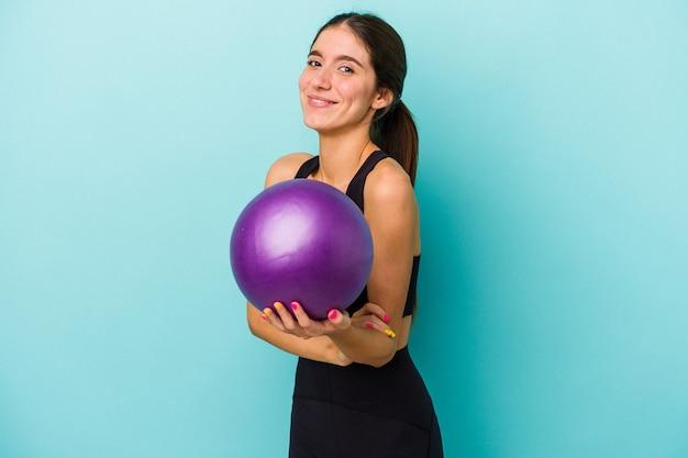 Mulher jovem aptidão caucasiana segurando uma bola isolada no fundo azul, rindo e se divertindo.