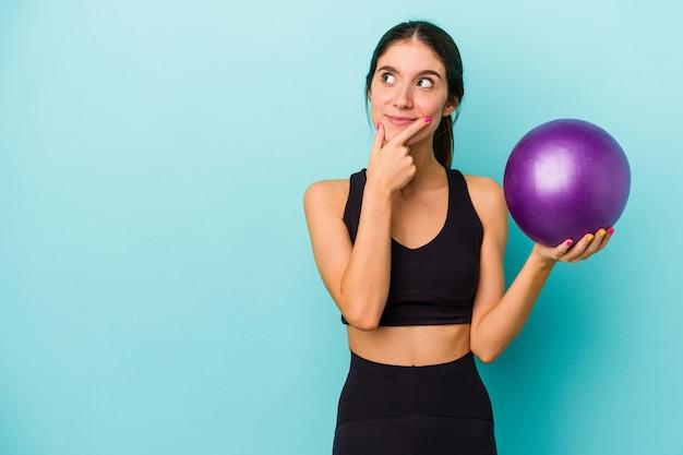 Mulher jovem aptidão caucasiana segurando uma bola isolada sobre fundo azul, olhando de soslaio com expressão duvidosa e cética.