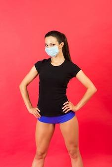 Mulher jovem aptidão chocada em máscara facial estéril sportswear malhando isolado no retrato de estúdio de fundo amarelo. conceito de estilo de vida de motivação de esporte treino. simule o espaço da cópia. espalhando as mãos