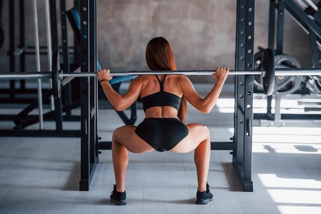 Mulher jovem aptidão com tipo de corpo magro, fazendo exercícios usando a barra. visão traseira.