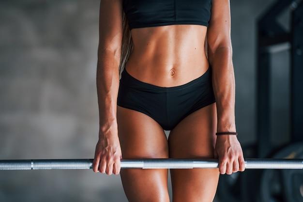 Mulher jovem aptidão com tipo de corpo magro, fazendo exercícios usando a barra.