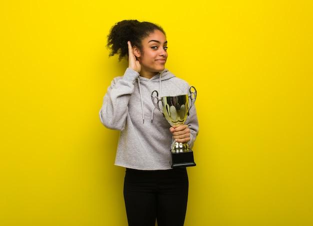 Mulher jovem aptidão negra tentar ouvir uma fofoca. segurando um troféu.