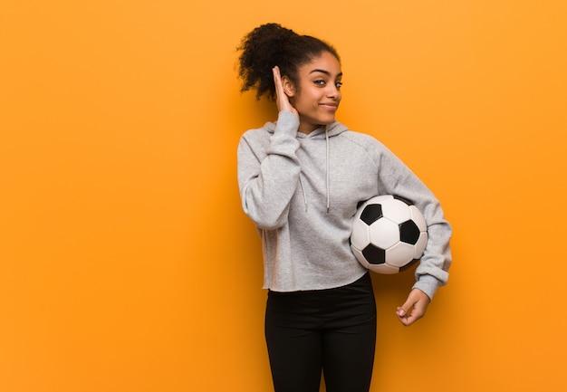 Mulher jovem aptidão negra tentar ouvir uma fofoca. segurando uma bola de futebol.