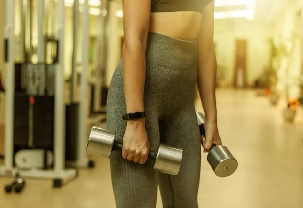Mulher jovem aptidão no sportwear, segurando halteres na mão no ginásio. treino com pesos livres. cortar foto