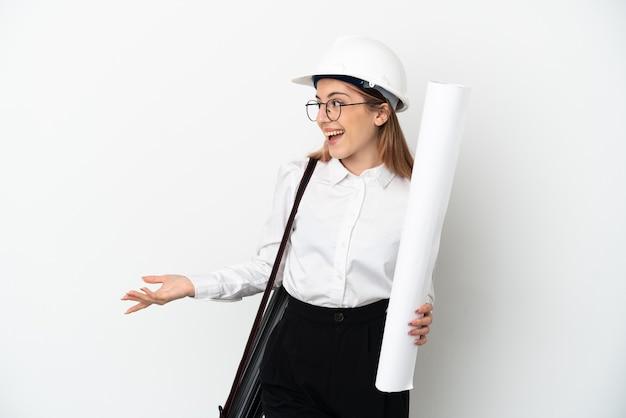 Mulher jovem arquiteta com capacete e segurando plantas isoladas na parede branca com expressão de surpresa enquanto olha para o lado