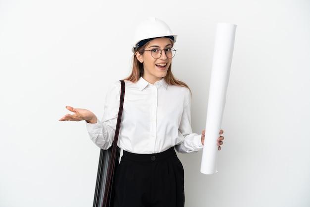 Mulher jovem arquiteta com capacete e segurando plantas isoladas na parede branca com expressão facial chocada