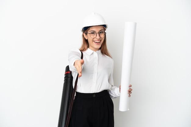 Mulher jovem arquiteta com capacete e segurando plantas isoladas no fundo branco apertando as mãos para fechar um bom negócio