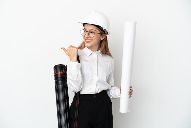 Mulher jovem arquiteta com capacete e segurando plantas isoladas no fundo branco apontando para o lado para apresentar um produto