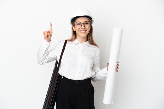 Mulher jovem arquiteta com capacete e segurando plantas isoladas no fundo branco apontando para uma ótima ideia