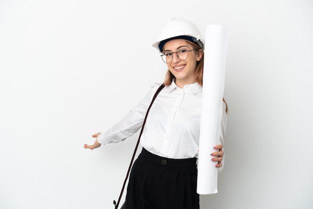 Mulher jovem arquiteta com capacete e segurando plantas isoladas no fundo branco, estendendo as mãos para o lado para convidar para vir