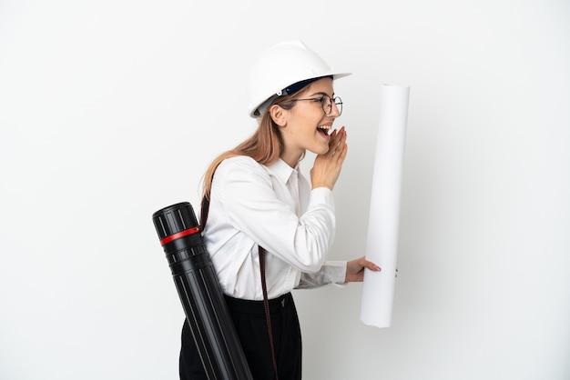 Mulher jovem arquiteta com capacete e segurando plantas isoladas no fundo branco, gritando com a boca aberta para o lado