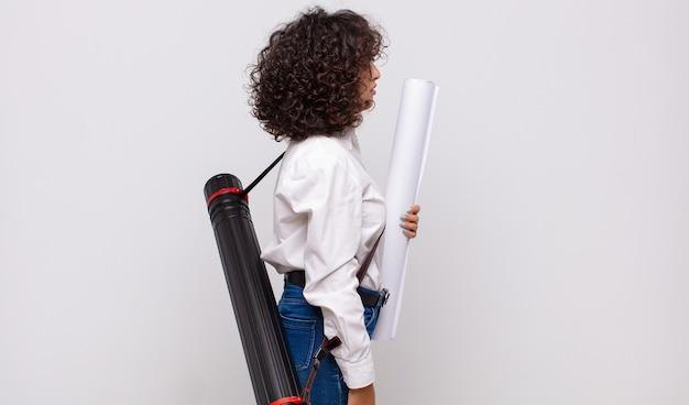 Mulher jovem arquiteta em vista de perfil, olhando para copiar o espaço à frente, pensando, imaginando ou sonhando acordada