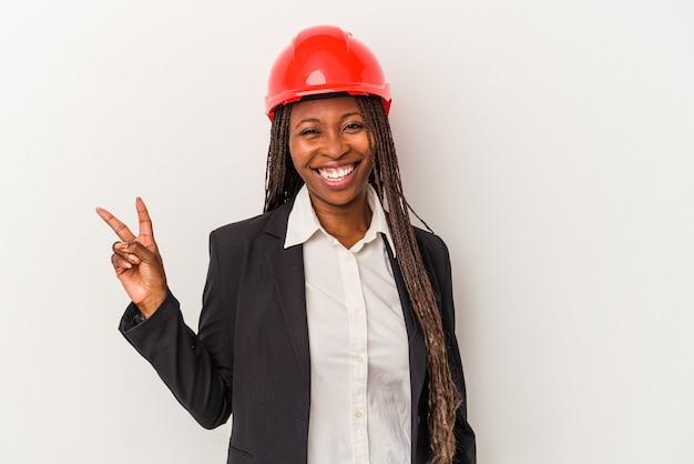 Mulher jovem arquiteto americano africano isolada no fundo branco alegre e despreocupada, mostrando um símbolo de paz com os dedos.