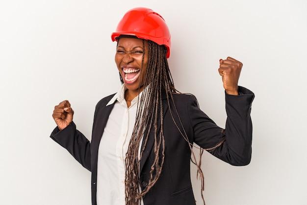 Mulher jovem arquiteto americano africano isolada no fundo branco, levantando o punho após uma vitória, o conceito de vencedor.