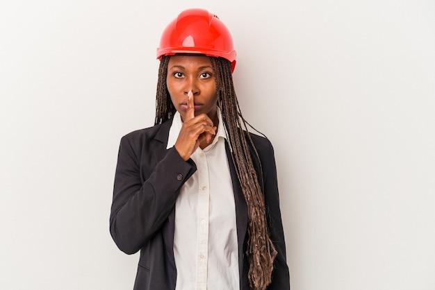 Mulher jovem arquiteto americano africano isolada no fundo branco, mantendo um segredo ou pedindo silêncio.