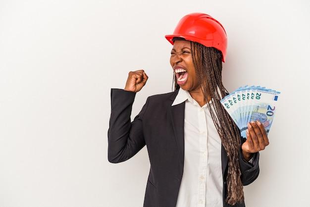 Mulher jovem arquiteto americano africano segurando contas isoladas no fundo branco, levantando o punho após uma vitória, o conceito de vencedor.