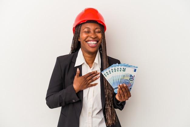 Mulher jovem arquiteto americano africano segurando contas isoladas no fundo branco ri alto, mantendo a mão no peito.