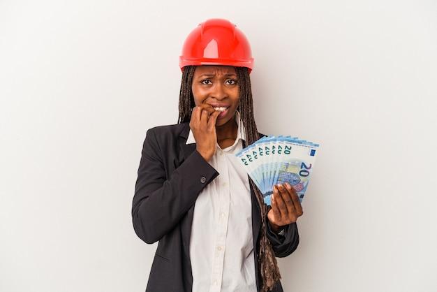 Mulher jovem arquiteto americano africano segurando contas isoladas no fundo branco, roendo as unhas, nervoso e muito ansioso.