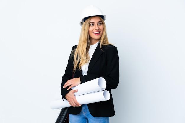 Mulher jovem arquiteto com capacete e segurando plantas sobre branco isolado, olhando para o lado