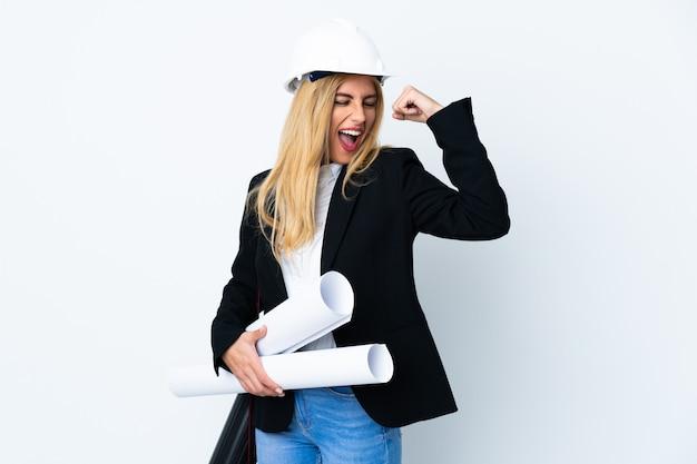 Mulher jovem arquiteto com capacete e segurando plantas sobre parede branca
