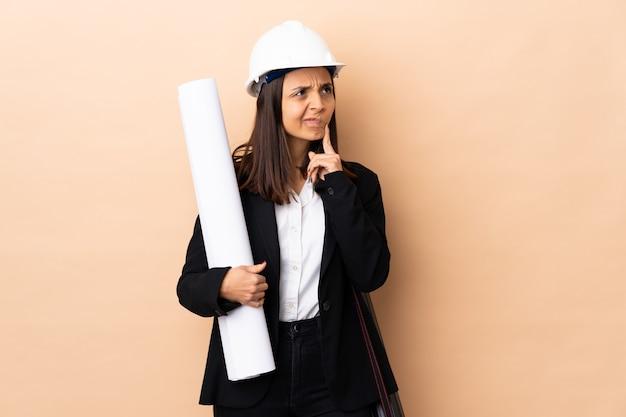 Mulher jovem arquiteto segurando plantas sobre parede isolada, tendo dúvidas enquanto olha para cima