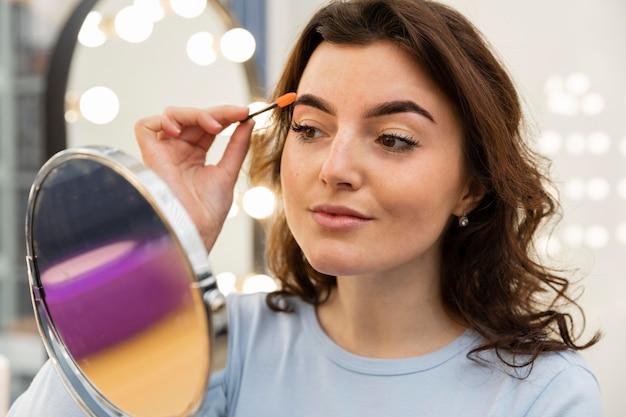 Mulher jovem arrumando as sobrancelhas