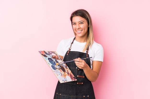 Mulher jovem artista caucasiana segurando um palete isolado feliz, sorridente e alegre.