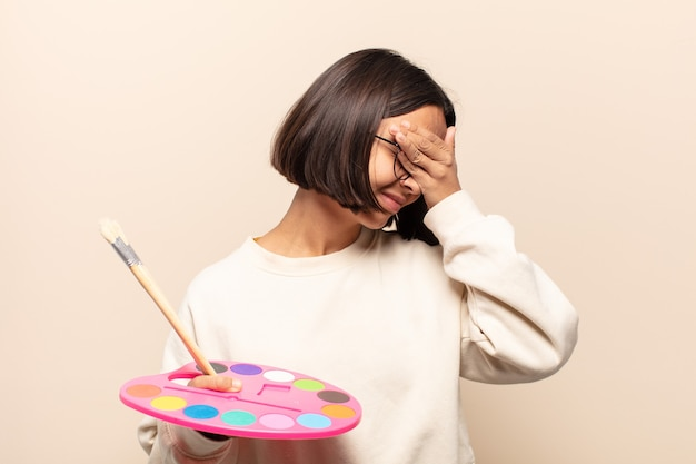 Mulher jovem artista cobrindo o rosto com a mão, gesto de palma da mão