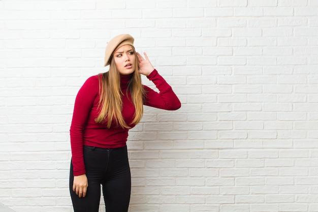 Mulher jovem artista olhando séria e curiosa, ouvindo, tentando ouvir uma conversa secreta ou fofoca, bisbilhotando