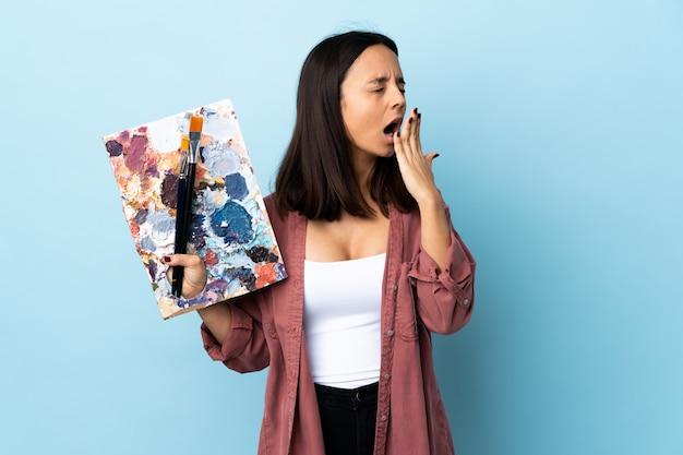 Mulher jovem artista segurando uma paleta na bocejar azul isolado e boca aberta grande coning com a mão