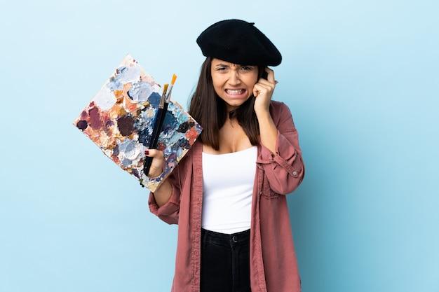 Mulher jovem artista segurando uma paleta nas orelhas frustradas e coning azuis isoladas