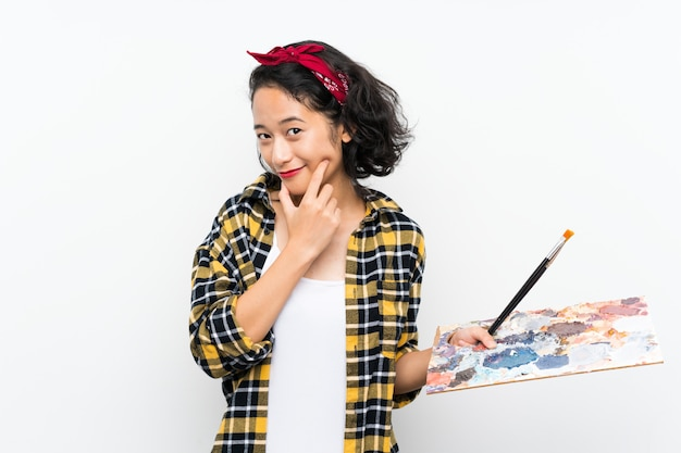 Mulher jovem artista segurando uma paleta pensando uma idéia e olhando de lado