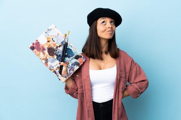 Mulher jovem artista segurando uma paleta sobre espaço azul isolado e olhando para cima