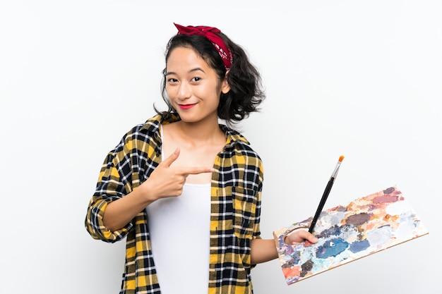 Mulher jovem artista segurando uma paleta sobre fundo branco isolado e apontando-o