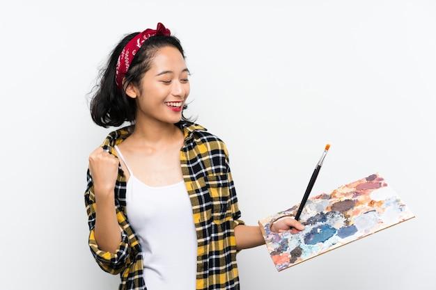 Mulher jovem artista segurando uma paleta sobre parede branca isolada, comemorando uma vitória