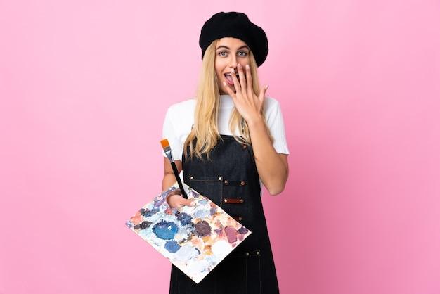 Mulher jovem artista segurando uma paleta sobre uma parede rosa isolada com expressão facial surpresa