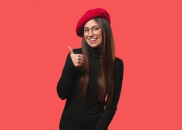 Mulher jovem artista sorrindo e levantando o polegar para cima