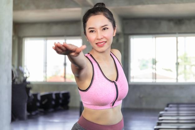 Mulher jovem ásia praticando ioga com sutiã sportswear e calças no ginásio de fitness.
