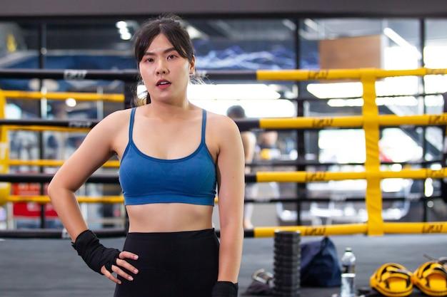 Mulher jovem asiática alegre fazendo exercício no ginásio