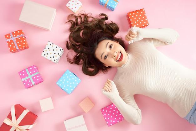 Mulher jovem asiática animada deitada no chão rosa com muitas caixas de presente coloridas.