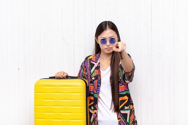 Mulher jovem asiática apontando para a câmera com os dois dedos e expressão de raiva, dizendo para você cumprir seu dever. conceito de férias