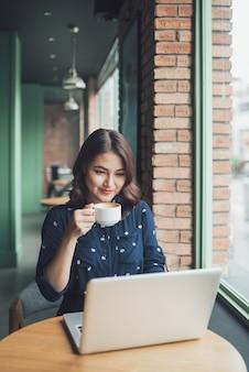 Mulher jovem asiática bonita bonita no café, desfrutar de um café sorrindo