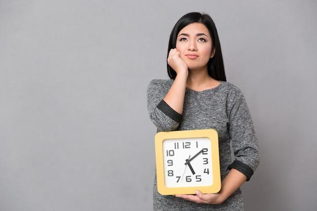 Mulher jovem asiática bonita em um macacão cinza esperando e segurando um grande relógio