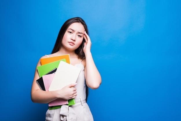 Mulher jovem asiática bonita lendo livro isolado na parede azul