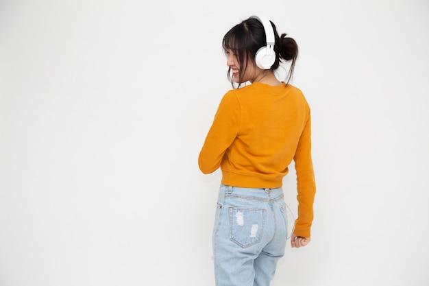 Mulher jovem asiática bonita ouvindo música com fones de ouvido no aplicativo de lista de reprodução de músicas em smartphone isolado no fundo branco