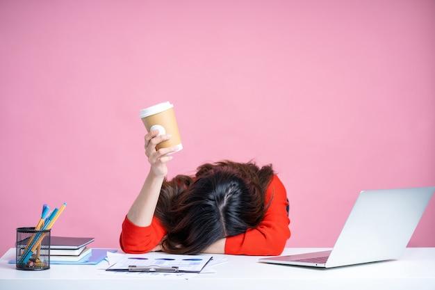 Mulher jovem asiática cansada de óculos e camisa branca. ela está segurando um café quente com um fundo rosa isolado.