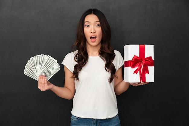 Mulher jovem asiática chocada segurando dinheiro e caixa de presente