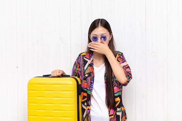 Mulher jovem asiática cobrindo o rosto com a mão. conceito de férias