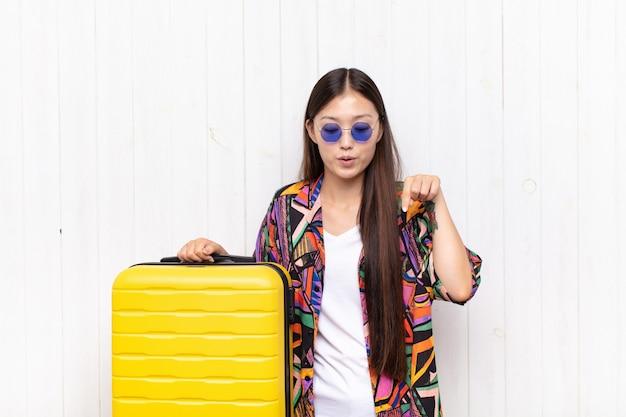 Mulher jovem asiática com a boca aberta apontando para baixo com ambas as mãos, parecendo chocada, espantada e surpresa. conceito de férias