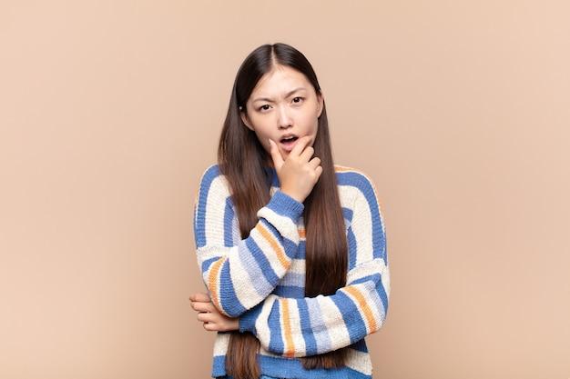 Mulher jovem asiática com boca e olhos bem abertos e mão no queixo, sentindo-se desagradavelmente chocada, dizendo o quê ou uau